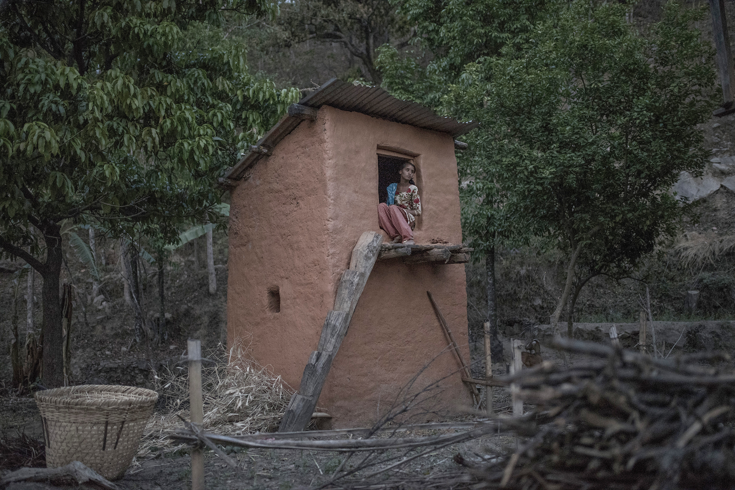 """Surekha, a 14-year-old girl from Achham district, poses for a portrait inside a """"goth"""" during her first period. This little mud house was built up several years ago in order to keep menstruating women away from their own houses, a tradition called """"Chhaupadi Partha"""". For the first time in Surekha's life, she will be considered impure and forced to live in this place for 7 days."""
